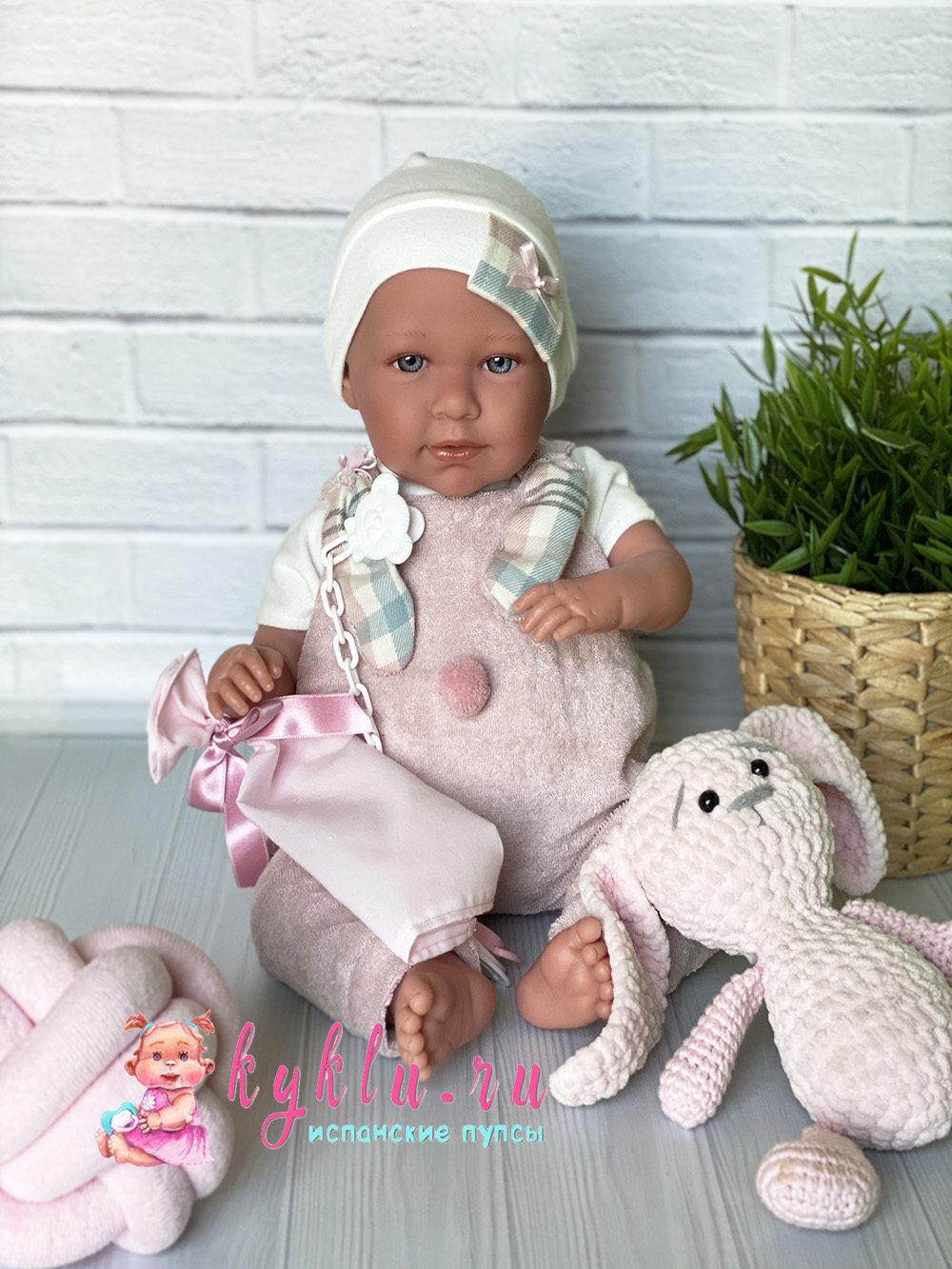Девочка младенец в бежевом комбинезоне